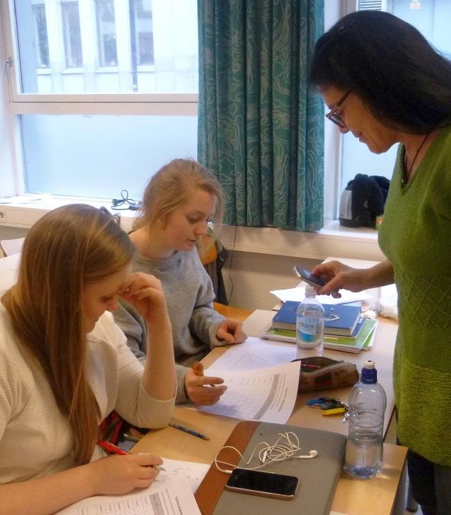 En lærer står over pulten til to elever og hjelper dem med matematikk