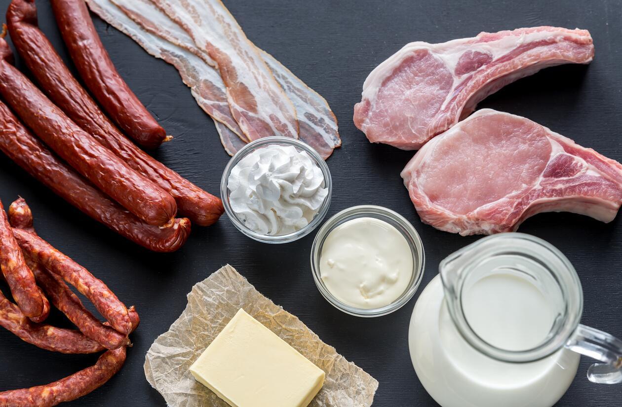 Foto av råvarer med mye mettet fett: Melk, smør, pølser, bacon, skinke,ost, m.m.