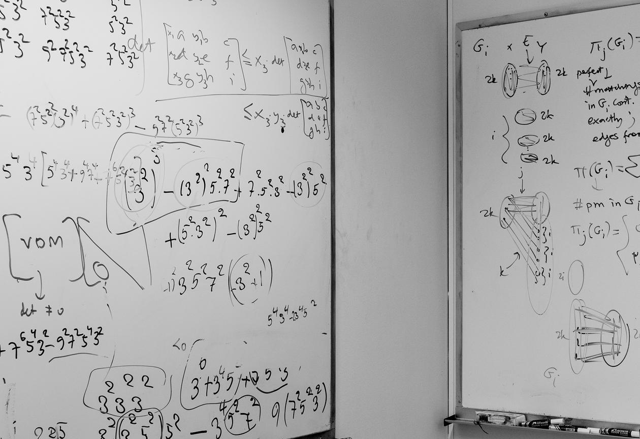 Photo showing two boards full of mathematical riddles, the picture is from the Bergen Algorithms Research Group's offices.