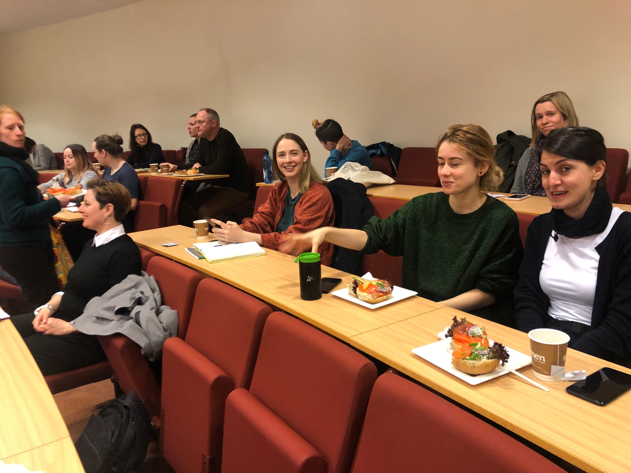 Photo of attendants of the lecture in the auditorium chatting and eating lunch