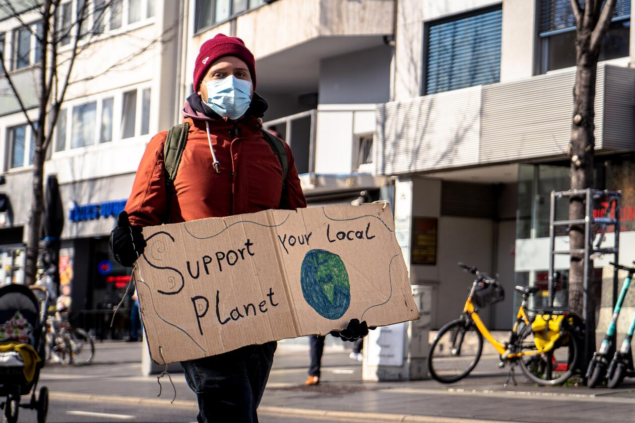 """Man with facemask, red cap and red jacket holds a homemade sign with the text """"Support your local planet"""" and an image of the globe"""
