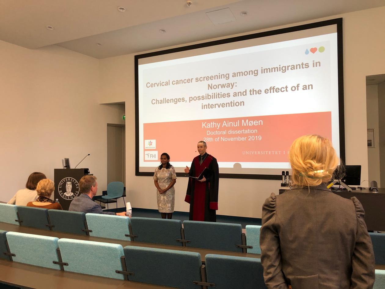 Doktorand Møen og disputasleder foran i et auditorium
