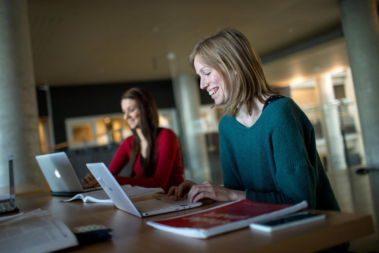 Two female students with computers, smiling