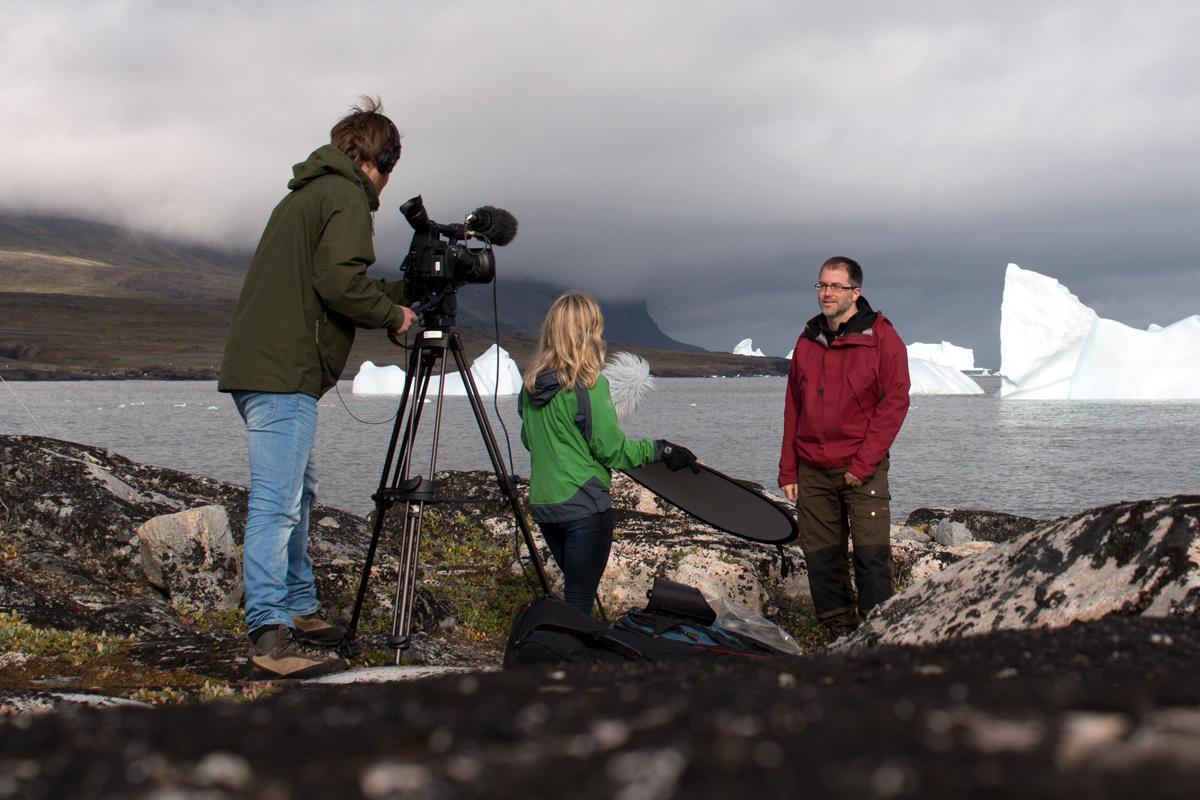 To personer filmer mann som står foran havet med isbreer i bakgrunnen