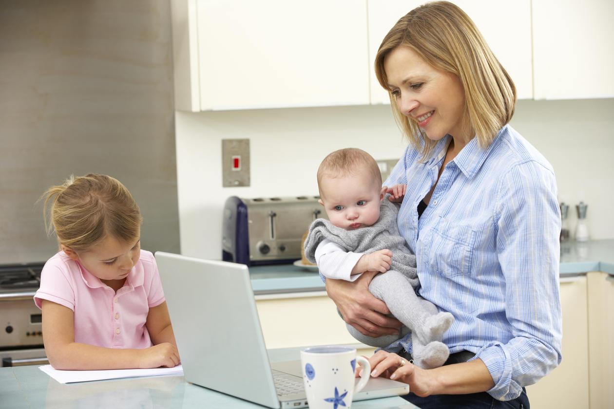 En mor med to barn oppholder seg på kjøkkenet. Mor jobber på datamaskinen mens hun holder minstemann.