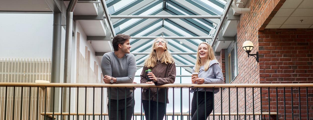 Tre studenter står på broen i Jussbygget