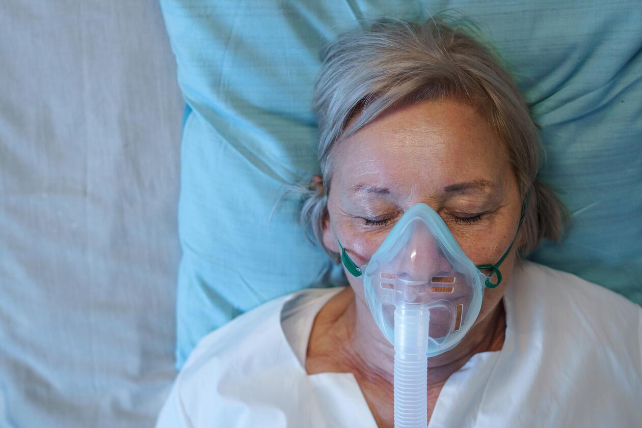 Eldre kvinne ligger på sykeseng med oksygenmaske på
