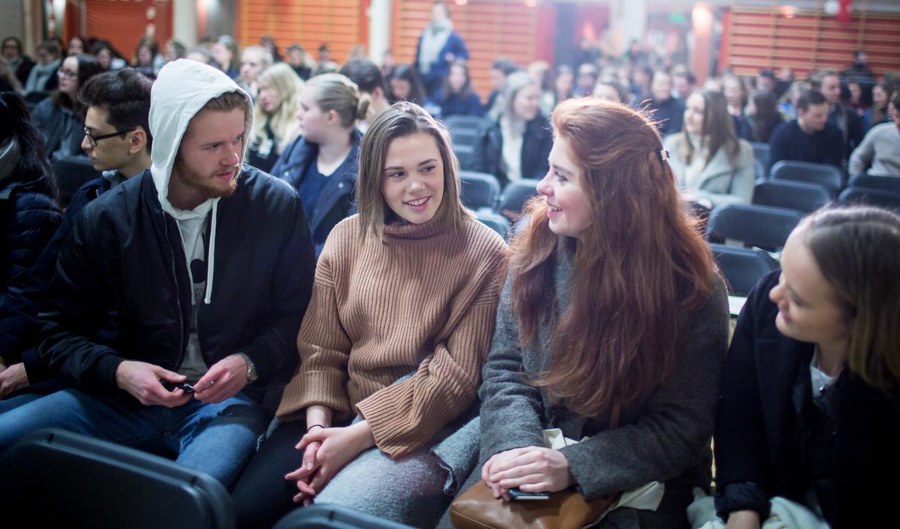Elever i en gymsal sittende på stoler, fokus på fire i forgrunnen