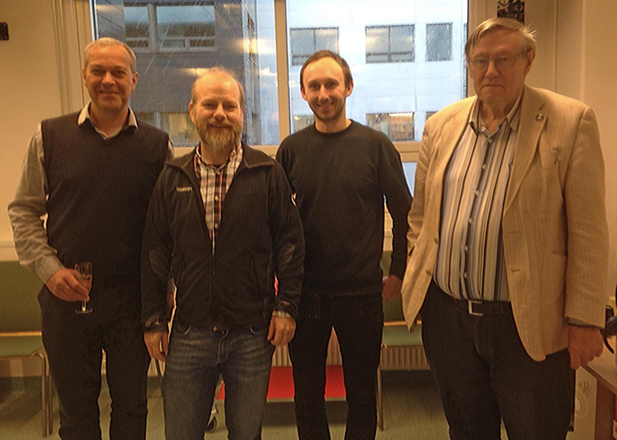 Ørjan Totland, John-Arvid Grytnes, Alistair Seddon, and John Birks standing in a line in a meeting room