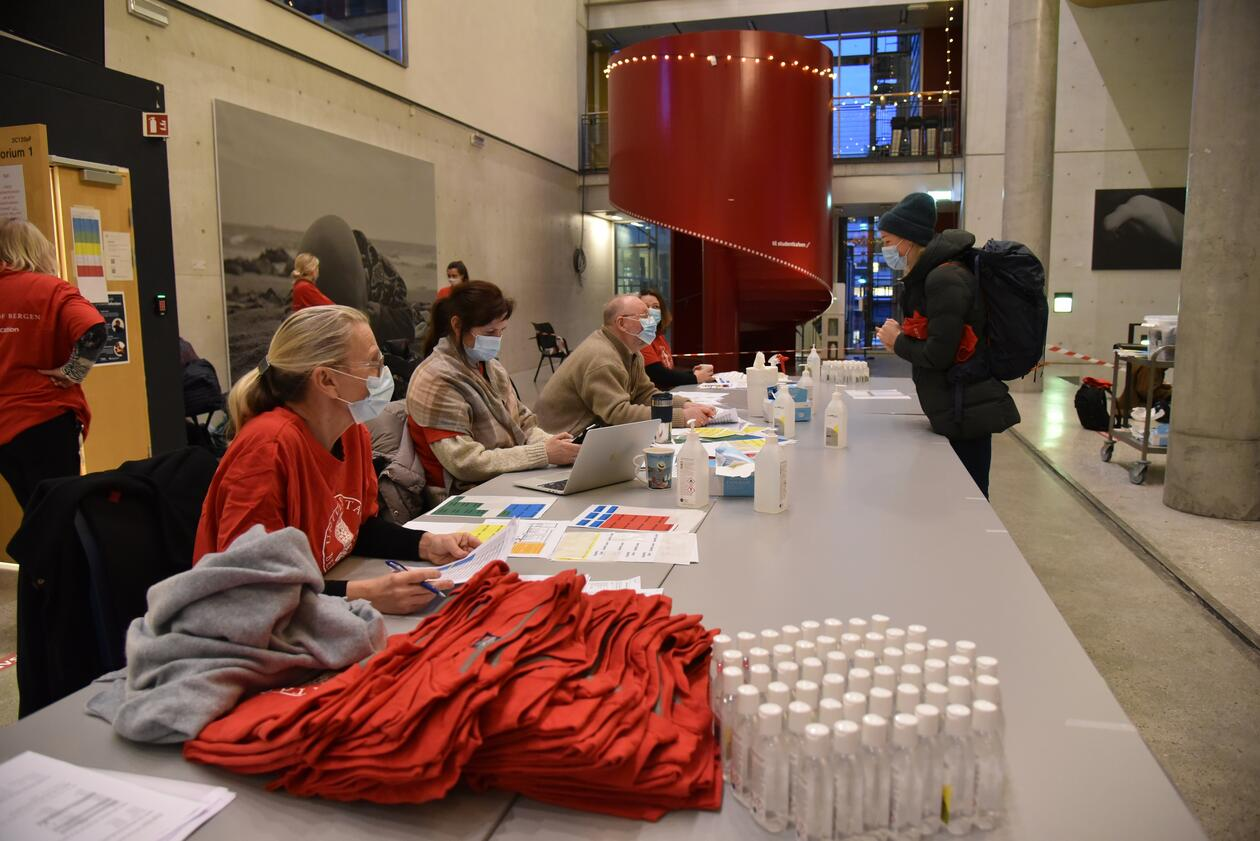 OSKE registrering, bord med personell med t-skjorter og antibacflasker. Student foran bordet som snakker med personell.