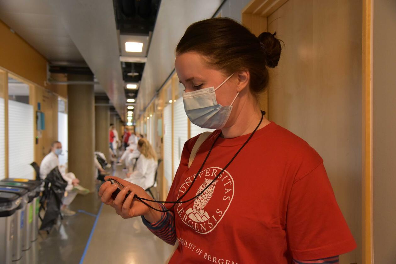 Personell i rød t-skjorte med munnbind på ser på en stoppeklokke utenfor eksamenslokalet. Mørkt hår, bundet sammen med en strikk. Studenter i bakgrunnen som venter på å komme inn