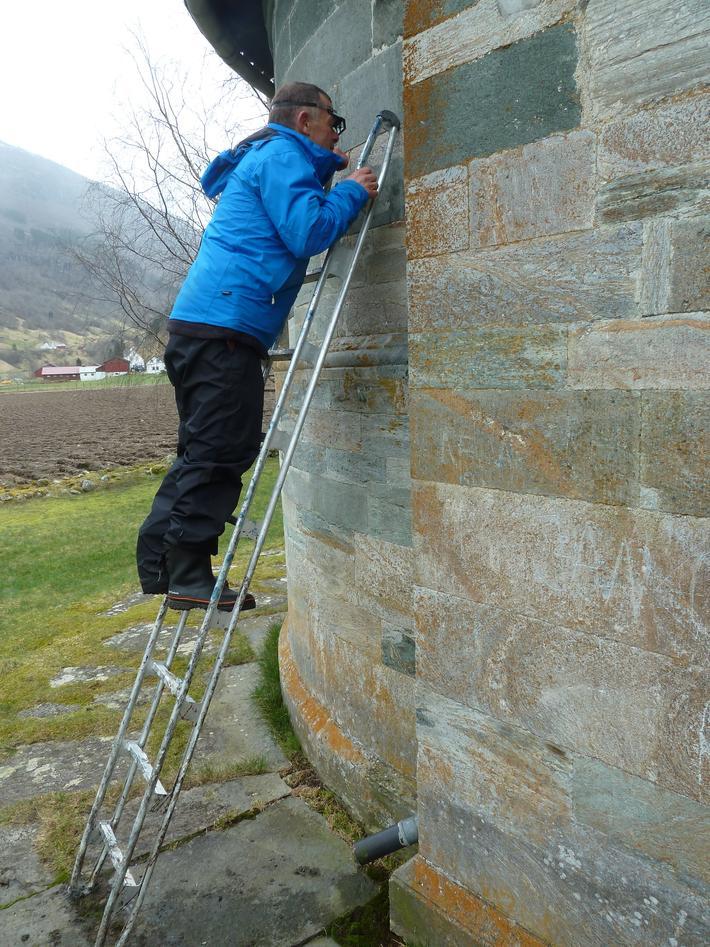 Geolog Øystein Jansen studerer bygningstein av kleber, Hove kyrkje, Vik i Sogn