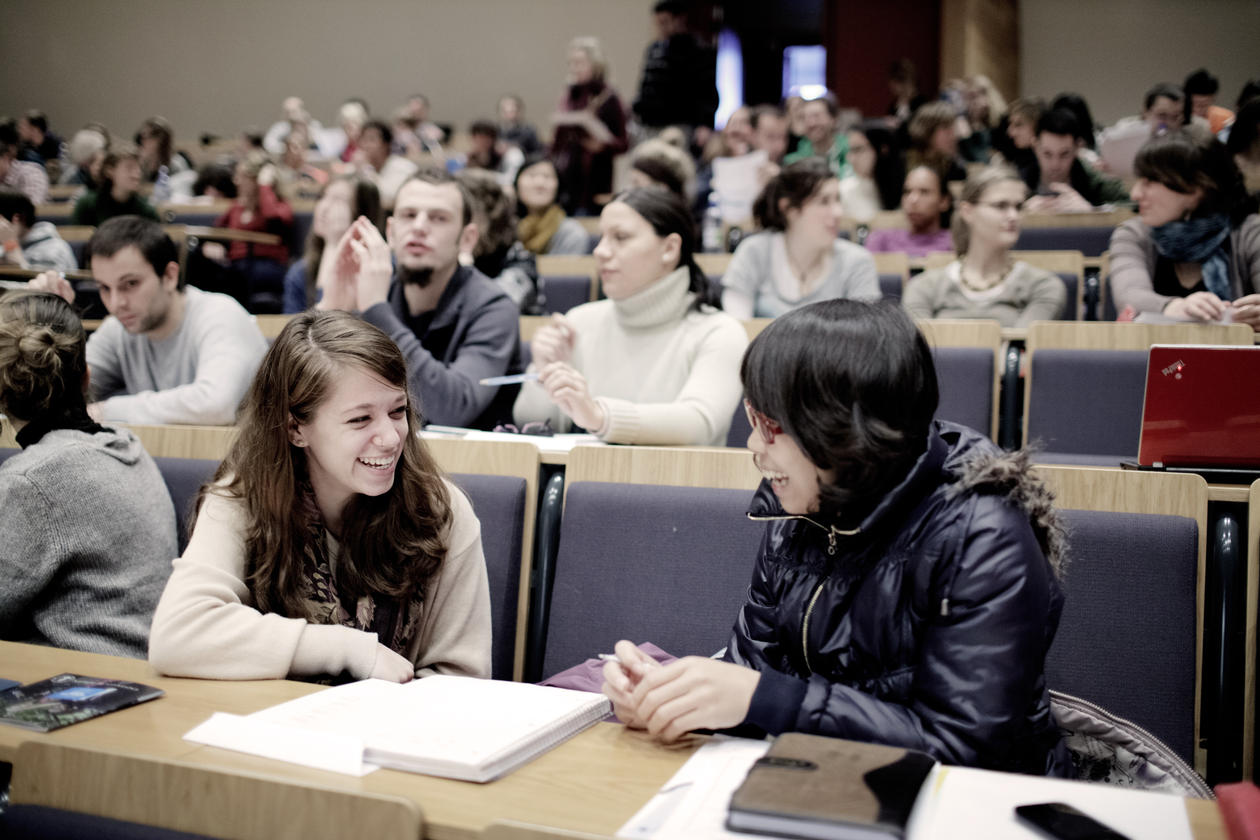 Bilde av studenter som snakker sammen i forelesningssal.
