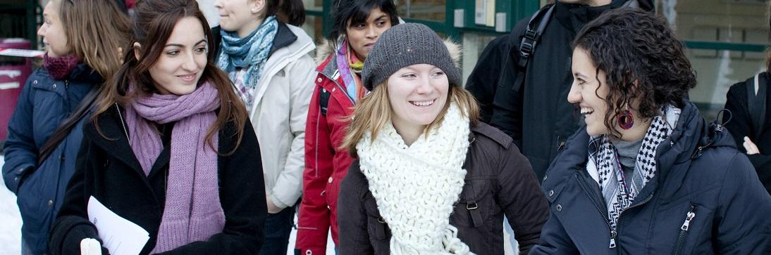Three female students looking at eachither, smiling, in winter clothes