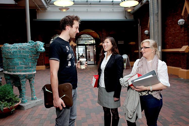 Tre studenter fra jusstudiet står og snakker sammen.