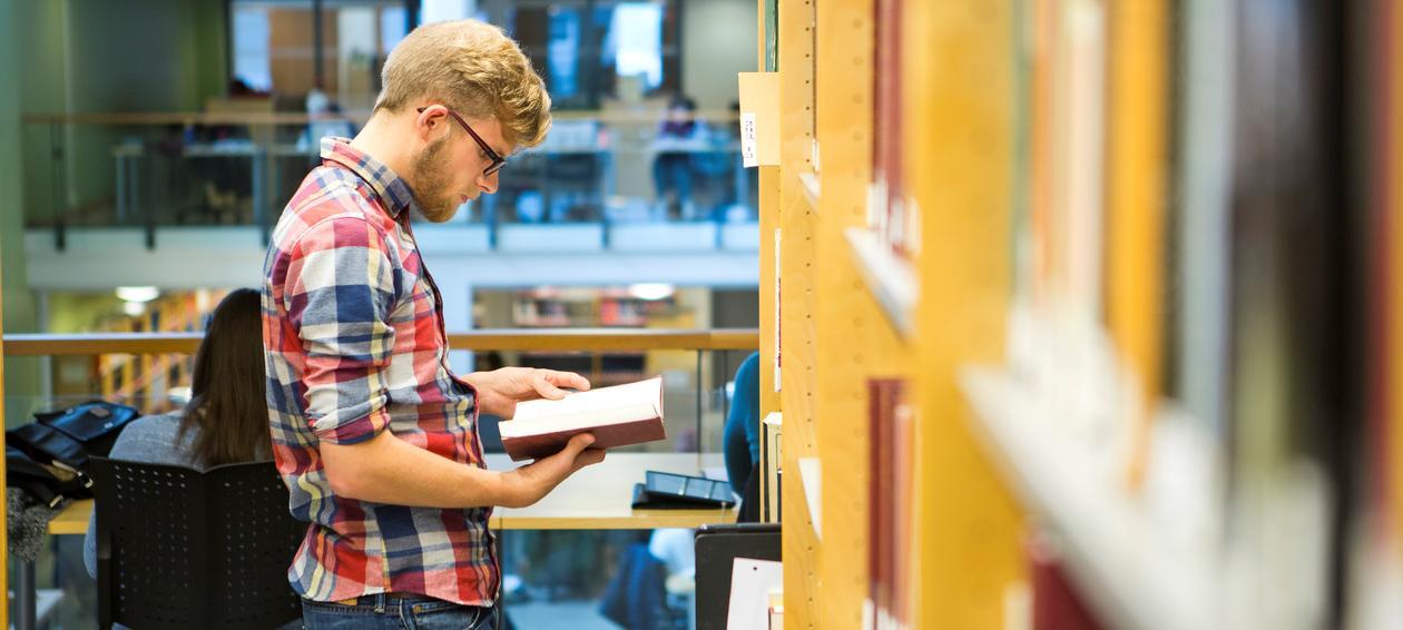 Mannlig student som står og leser ved en bokhylle på biblioteket