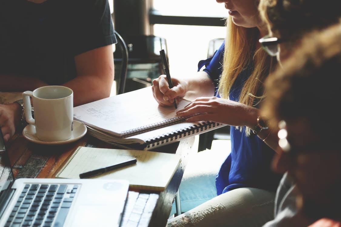 Kvinne skriver. Mennesker rundt et bord.