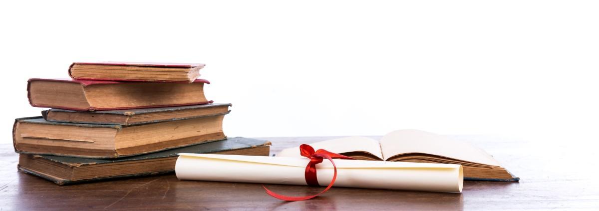 PhD diplom liggende ved en bunke eldre bøker