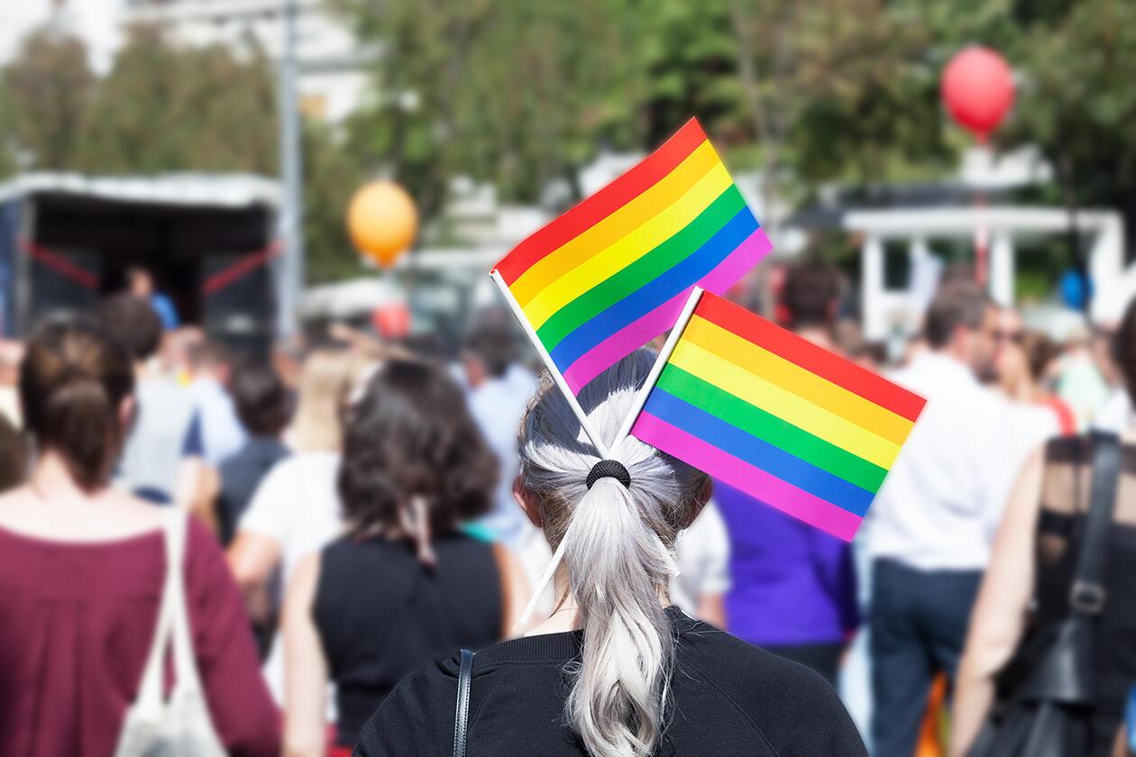 Dame med regnbueflagg i folkemengde.