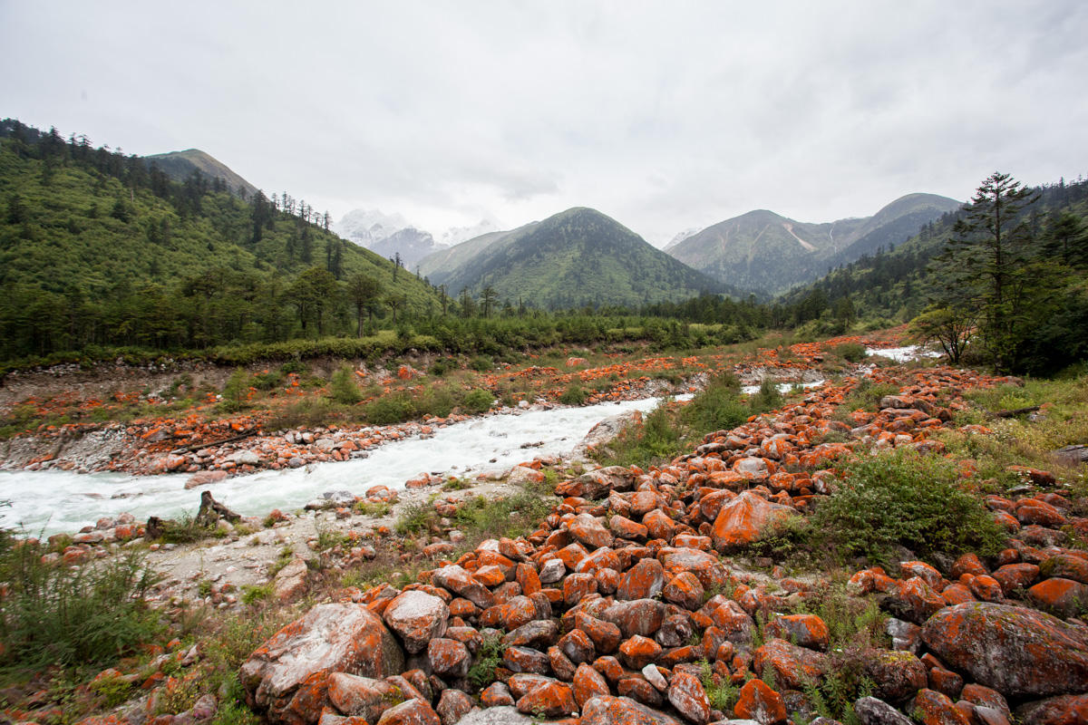 Landscape view looking upriver towards mountains in Sichuan, China, with large rounded boulders on the side of the river covered in red lichens