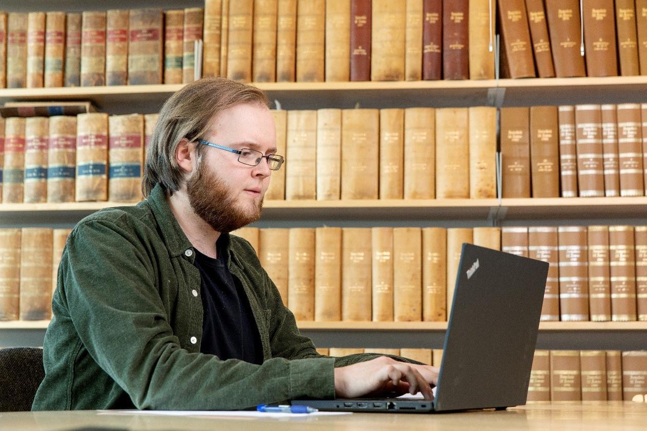 En ph.d.-student skriver på PC foran en bokhylle