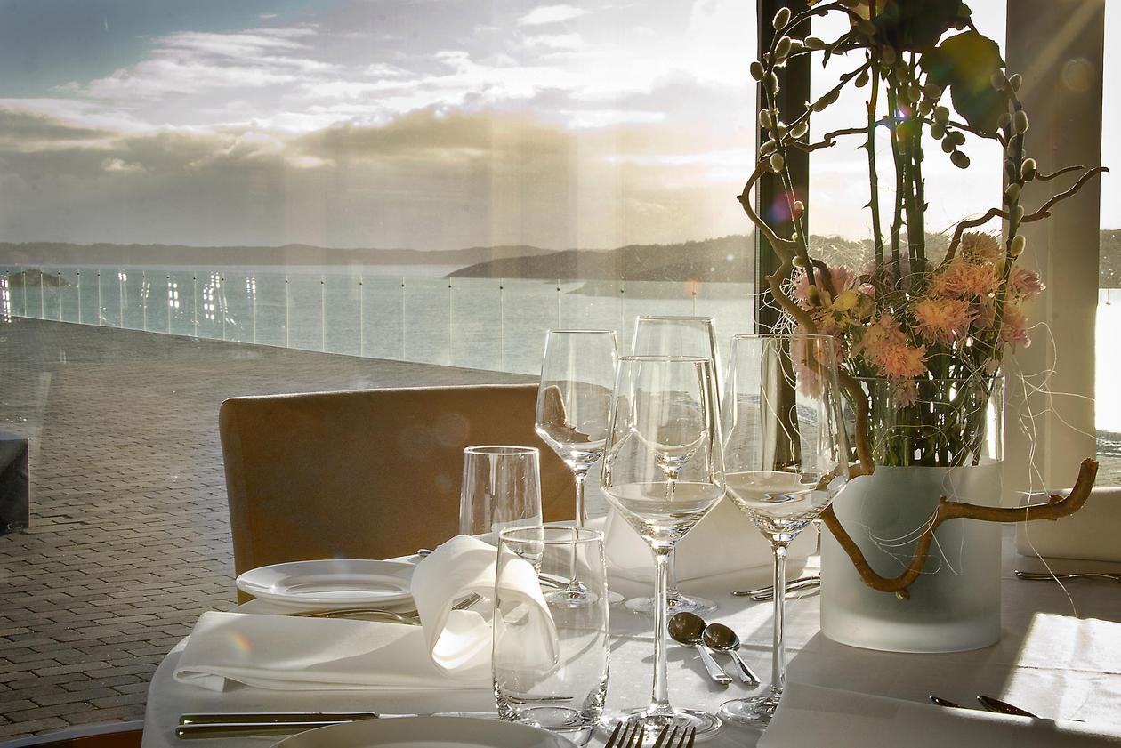 Photo taken from the restaurant, showing a nicely set table, and an amazing view of the ocean behind.