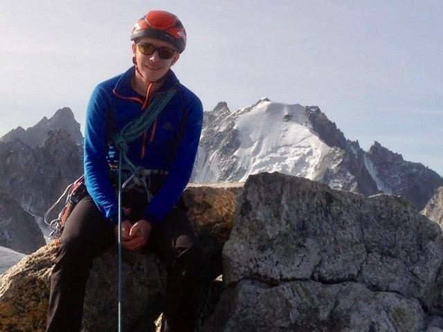 Richard Payne in climbing gear sitting on a rock