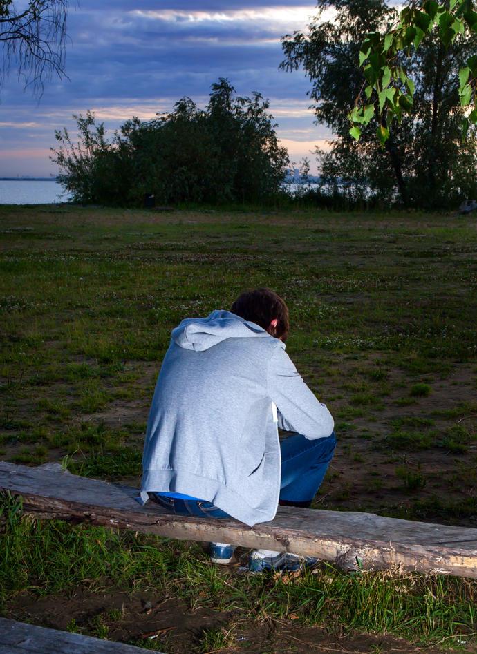 Trist ung mann som sitter med ryggen til på en benk i en park i skumringen