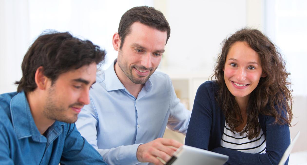 Tre personer som smiler og ser på lesebrett