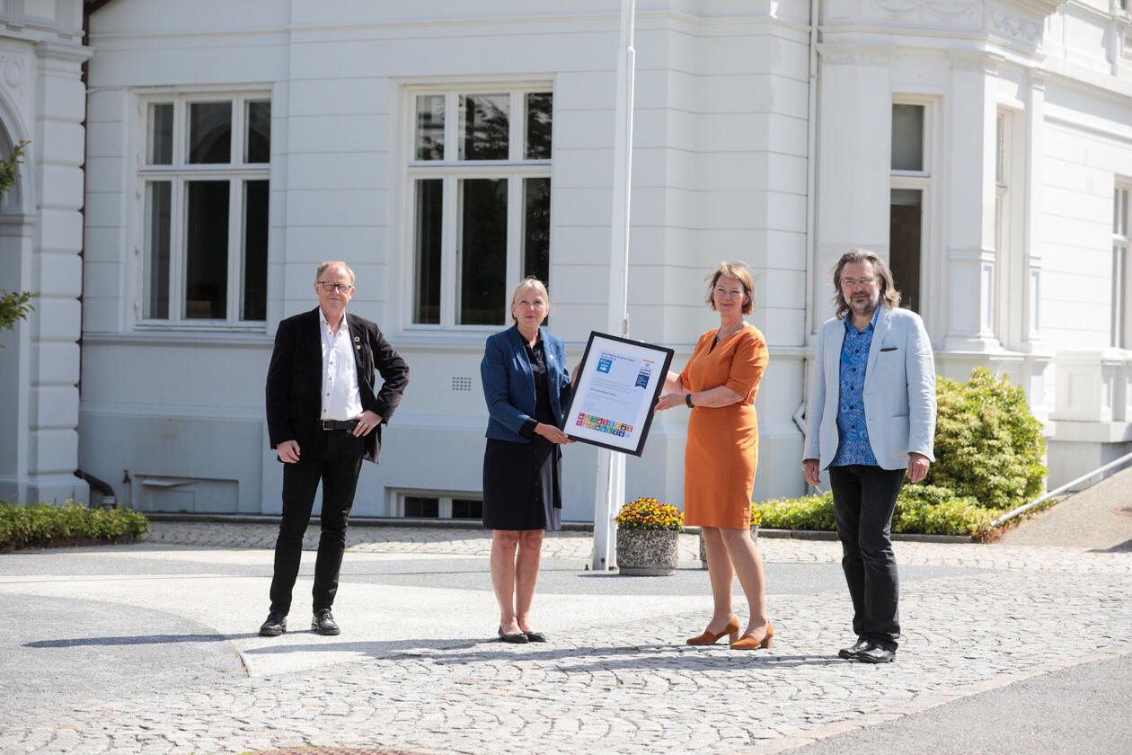 Rector Margareth Hagen is handed a UN certificate from Lise Øvreås of SDG Bergen Ocean for the University of Bergen becoming UNAI SDG14 Hub 2021-2024 with Marine Director Amund Maage (left)  and Edvard Hvidingi of SDG Bergen Science Advice (right).