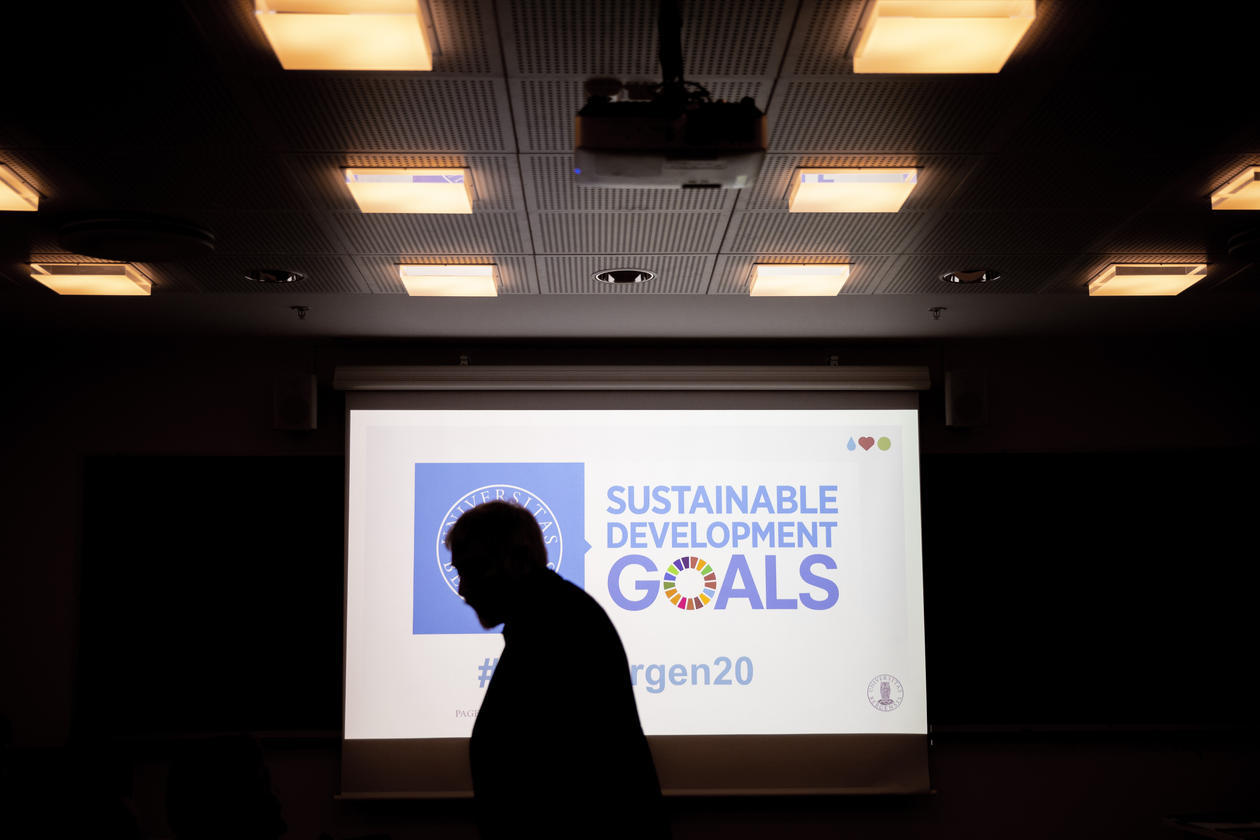 Silhouette of man in a darkened room against conference room screen during SDG Bergen Science Advice workshop on 5 February 2020.