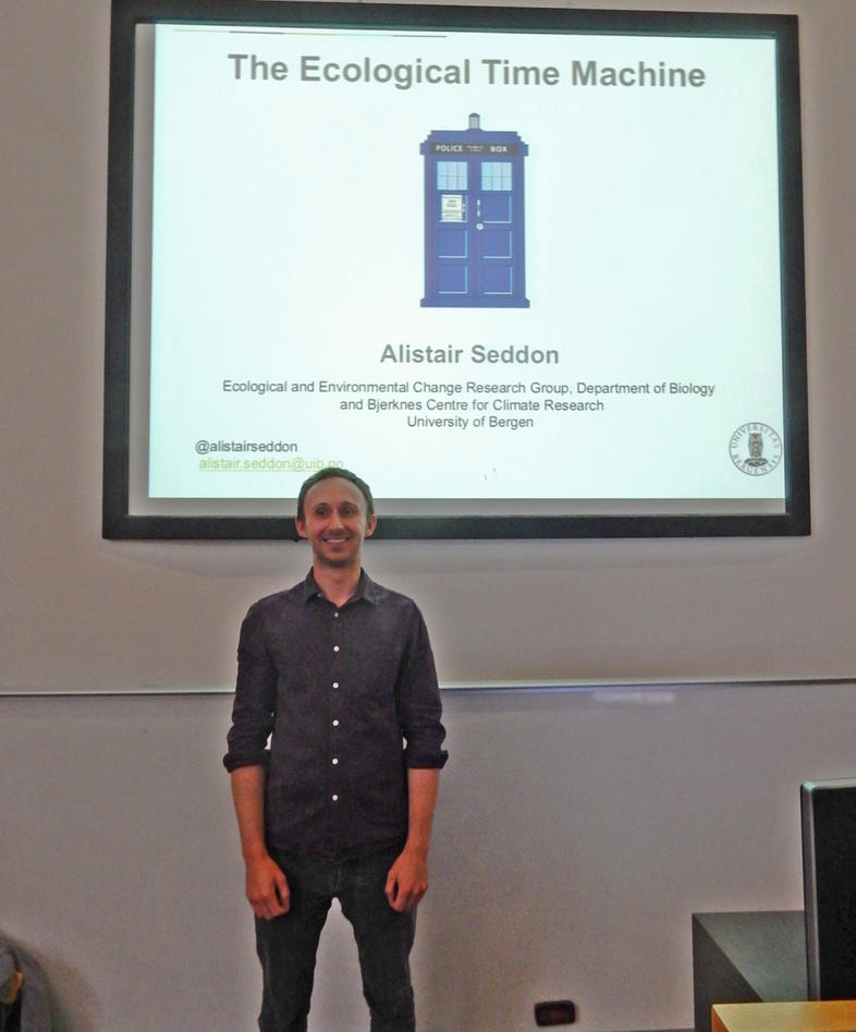 Alistair Seddon standing before the title slide of his lecture called The Ecological Time Machinee