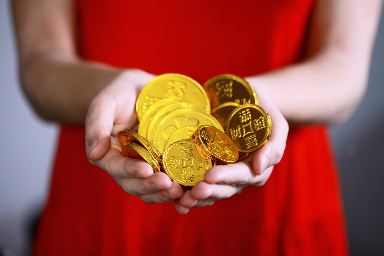 Kvinne i rød kjole holder fram en håndfull gullpenger