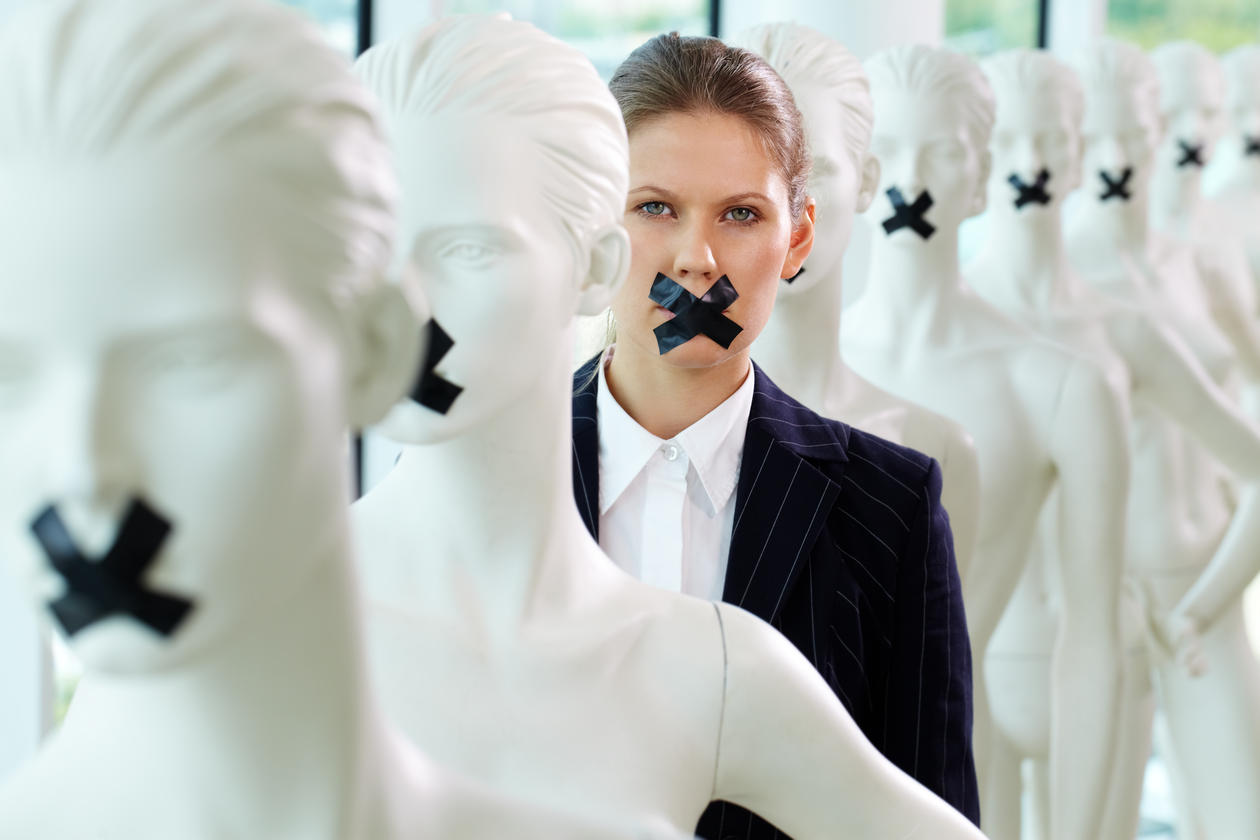 A woman standing in line of mannequins with taped mouth, stock photo