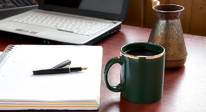 Skriveblokk med penn, kaffekopp og laptop i bakgrunnen