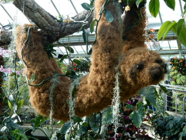 Sculpture of a sloth made from moss and other vegetation hanging from a branch