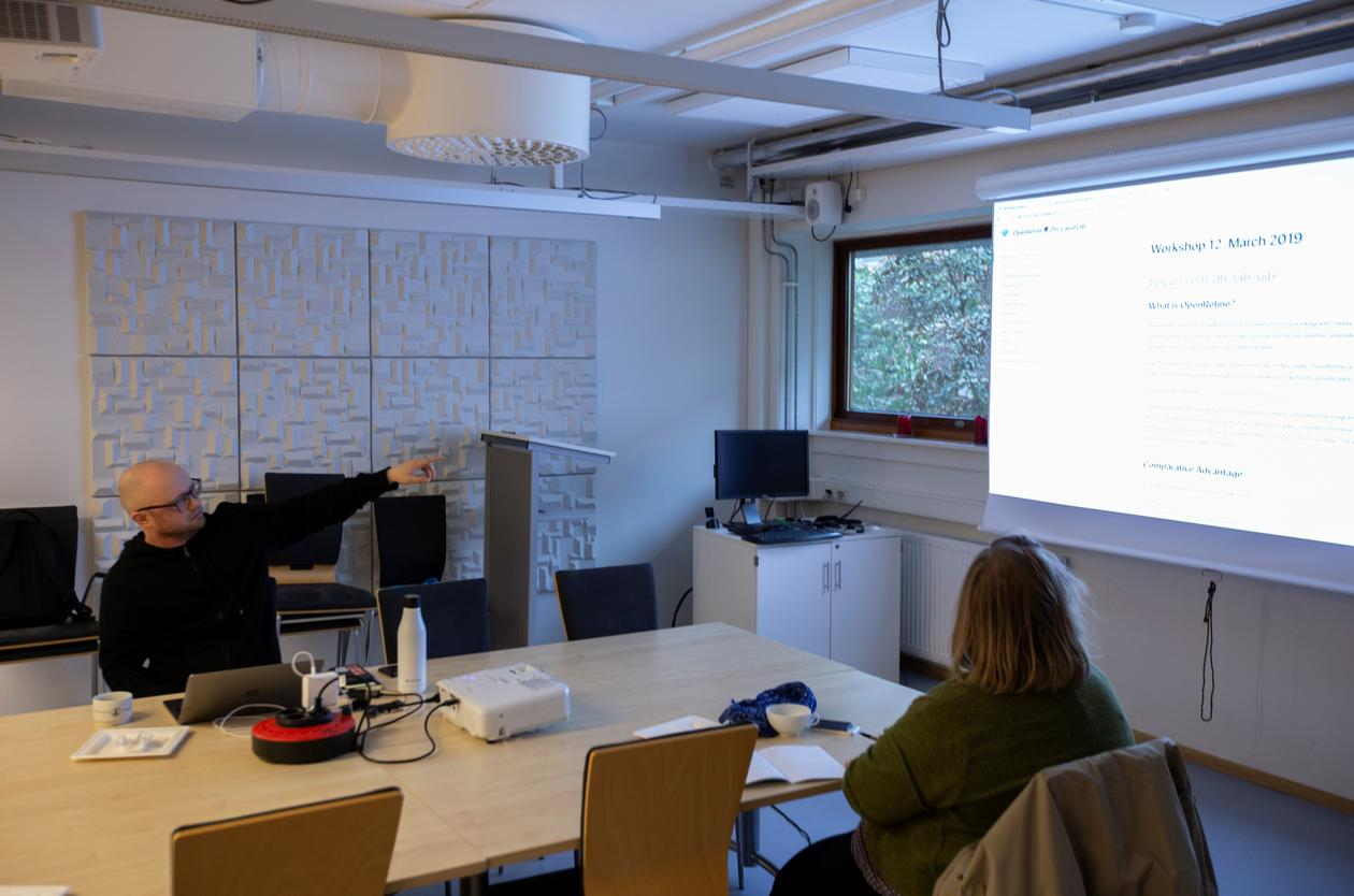 Tarje talks and points at the powerpoint presentation