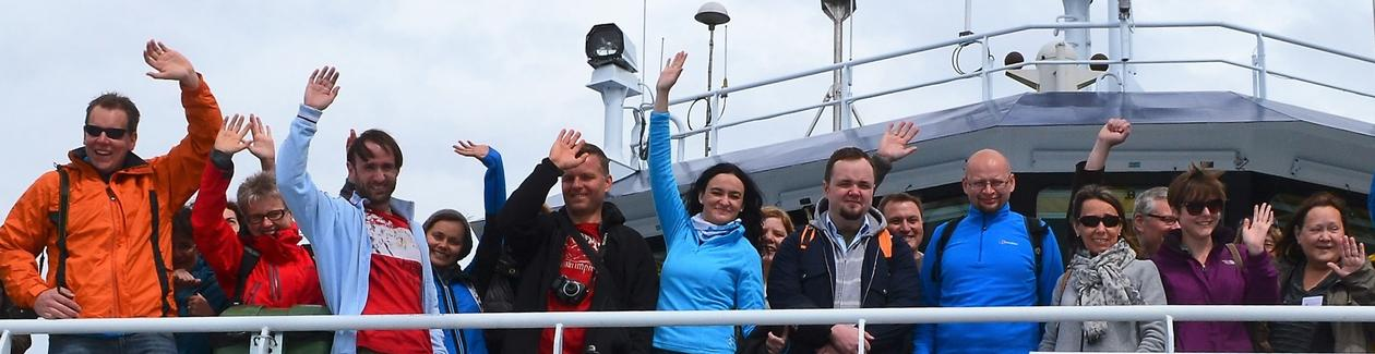 A group of people waving from the top deck of a ship.