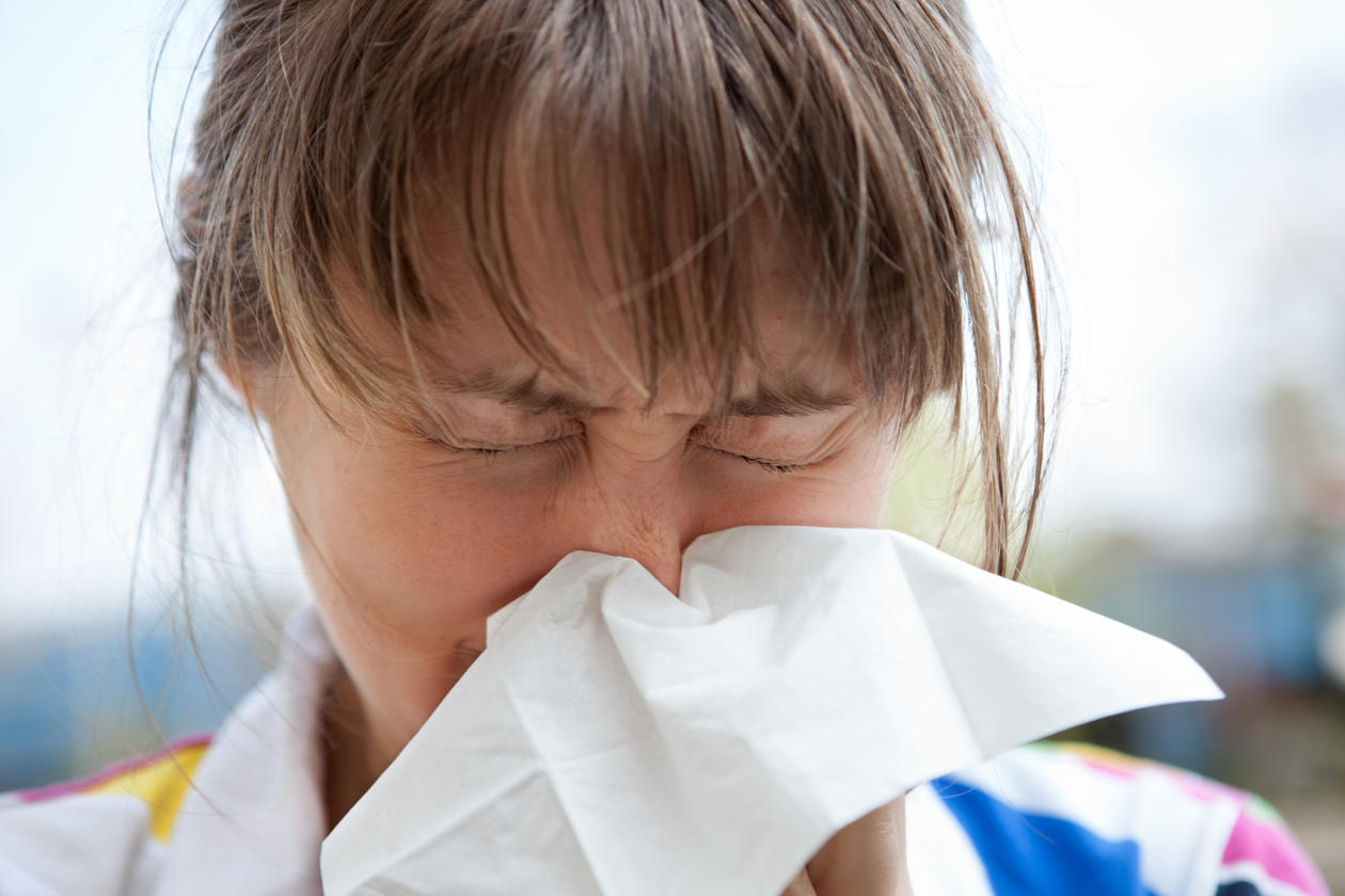 Allergic girl sneezing in a tissue