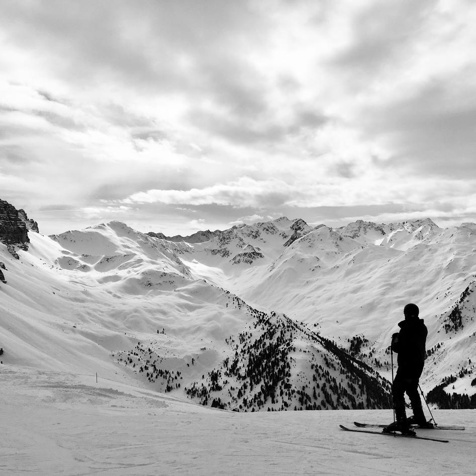 Skier looking out to snowy mountains