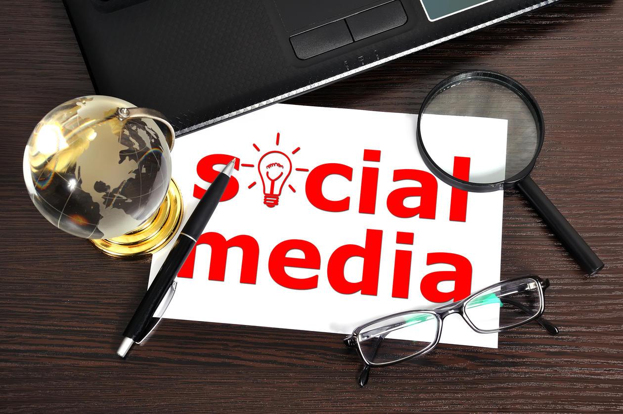 """Teksten """"Social media"""" med lupe, briller, globus og PC dandert rundt."""