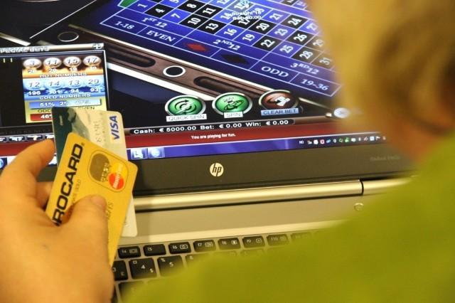 En person med flere kredittkort i hånden sitter foran dataskjermen og ser på et pengespill.