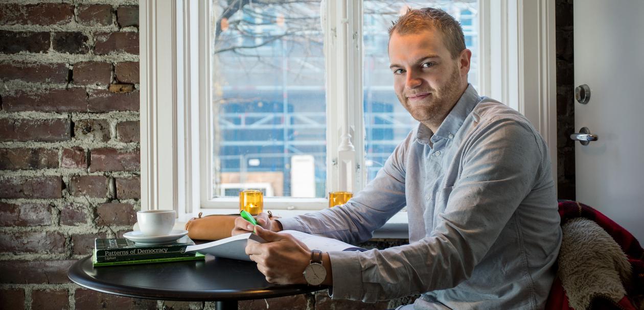 Ung mann sitter på kafe med bøker og en kaffe på bordet