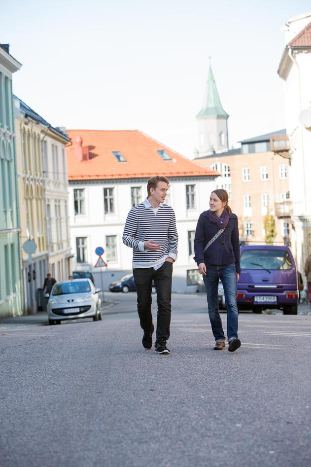 To studenter spaserer gjennom gatene, med SV-bygget i bakgrunnen.