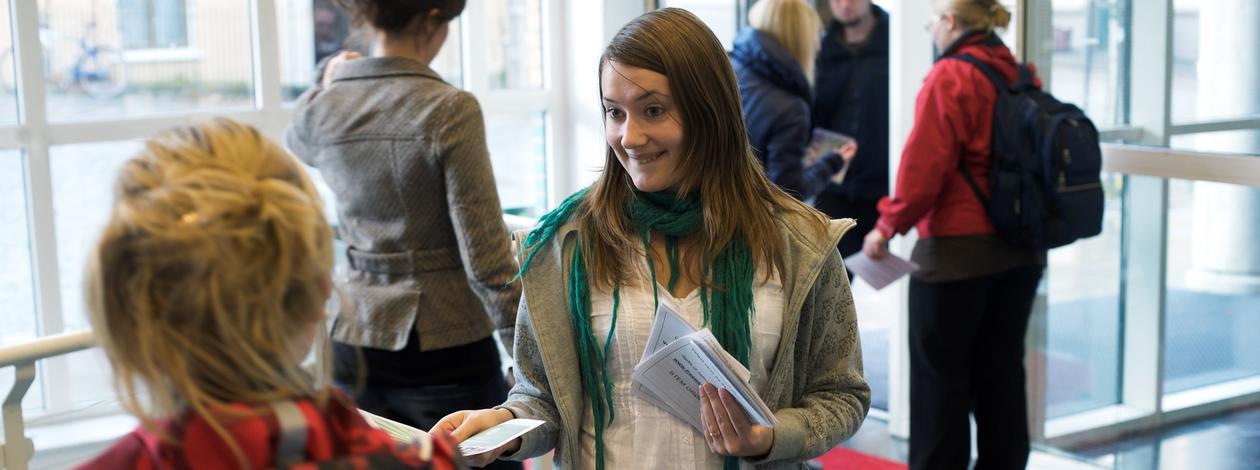 En jente deler ut flyers til studenter i inngangspartiet til SV-bygget