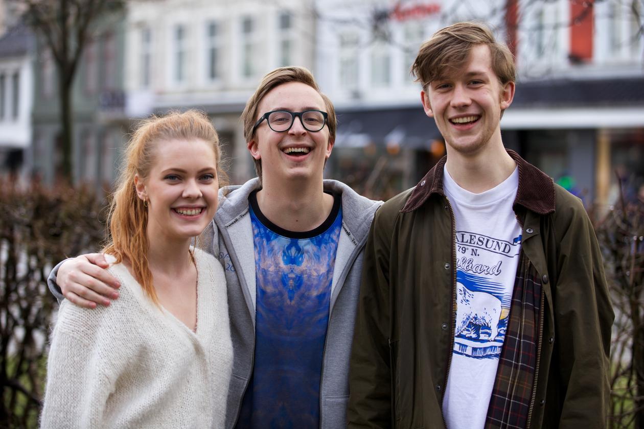 Tre engasjerte studenter smiler mot kamera med hus og park i bakgrunnen.