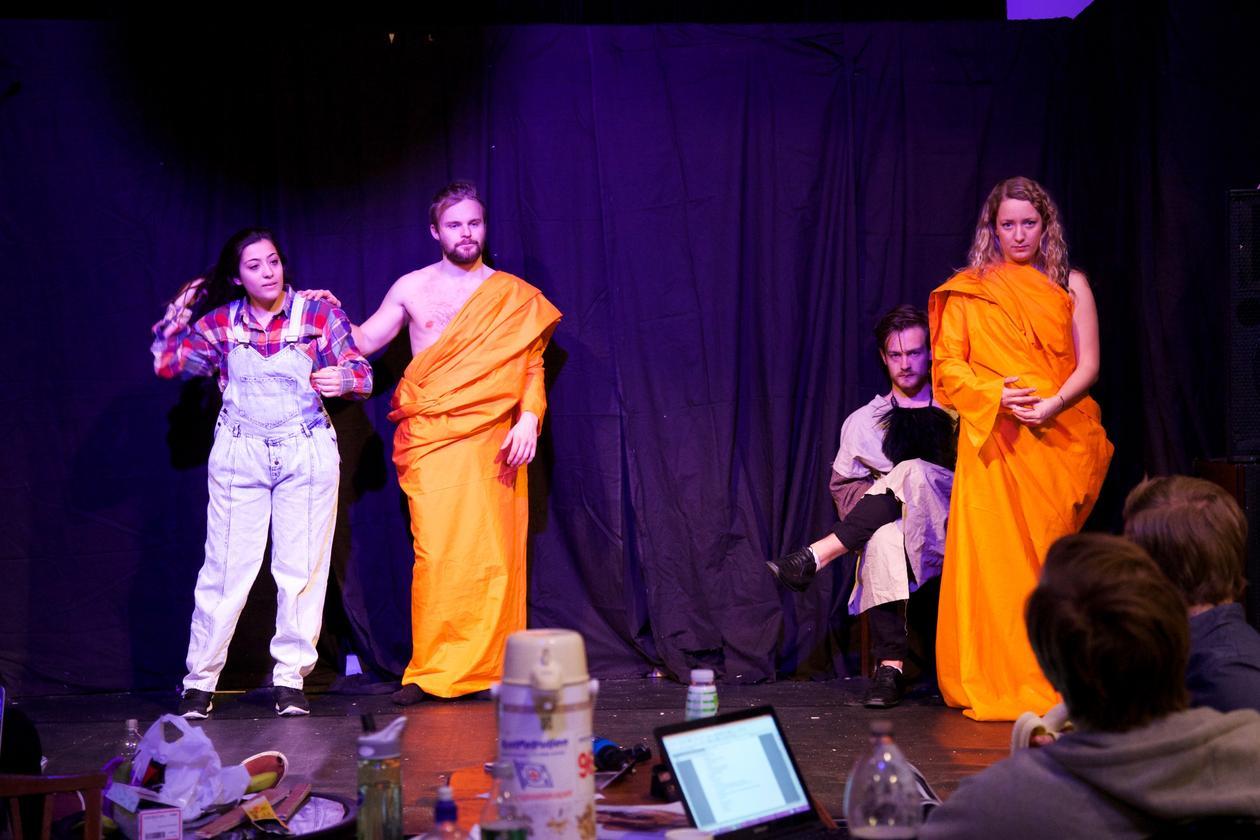 Fire skuespillere står på scenen i forskjellige kostymer.