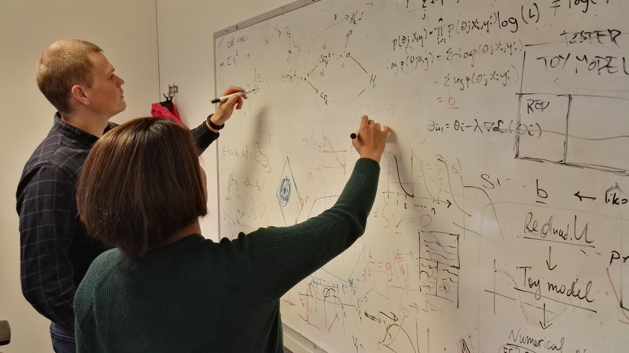 Mathematicians working on a white board with complex algorithms