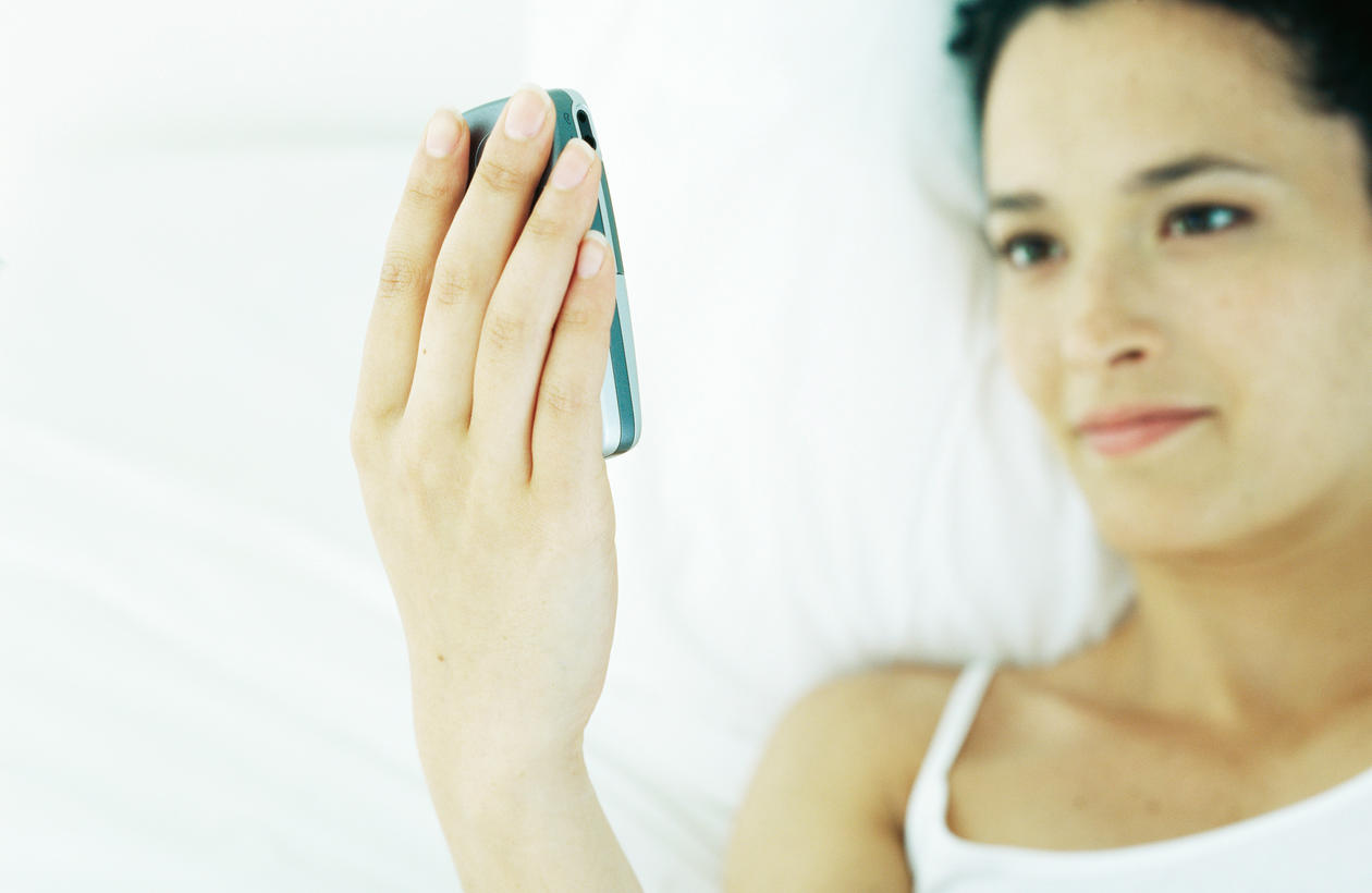 Woman lying in a bed whilst holding a mobile phone in her hand.
