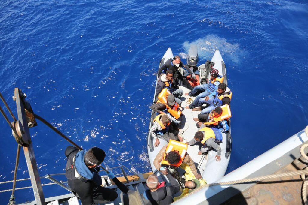 Migrants boarding a ship in the Mediterranean.